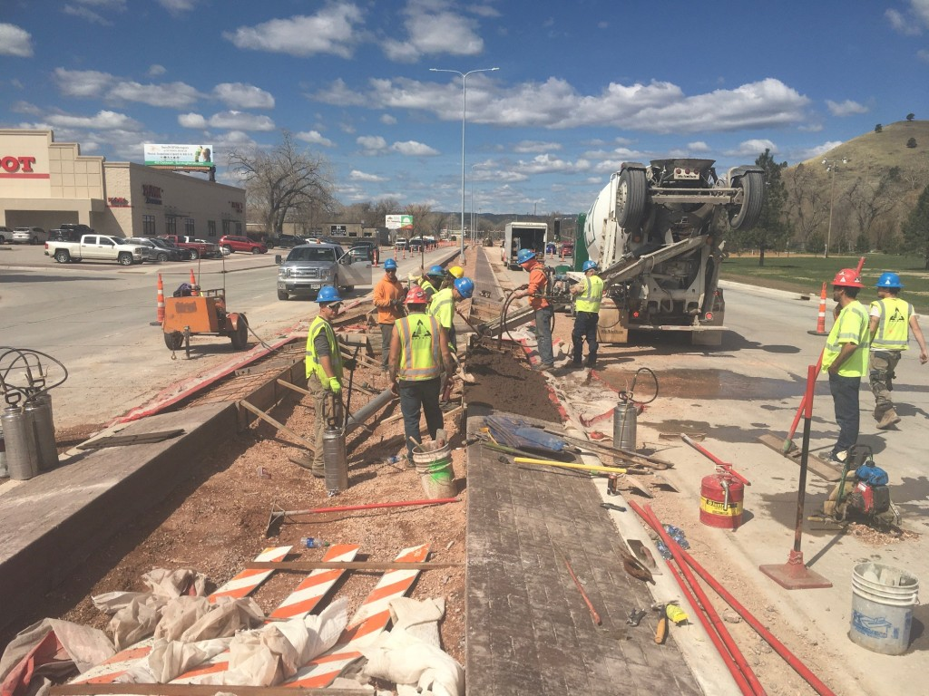 Construction Crew Installing Colored Median Barrier Pavement on Omaha Street in Rapid City, South Dakota, Wednesday, April 28, 2021.